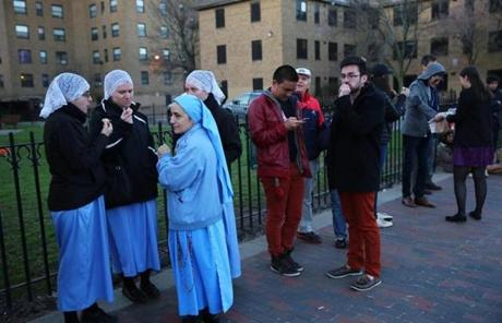 Daughters of Mary of Nazareth ate donuts while waiting in line for free tickets to a prayer service Thursday outside the Cathedral of the Holy Cross.
