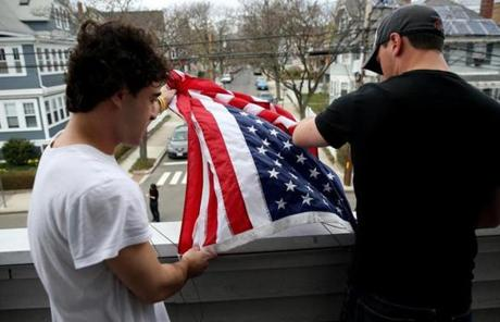 Tufts University students Thomas Isman, left, and Gary Grandonico hung a flag at their house, next to the home of Sean Collier.