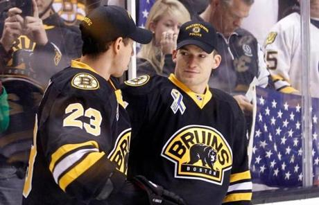 Andrew Ference, right, talked with Chris Kelly. The Bruins wore hats from local law enforcement agencies before the game.