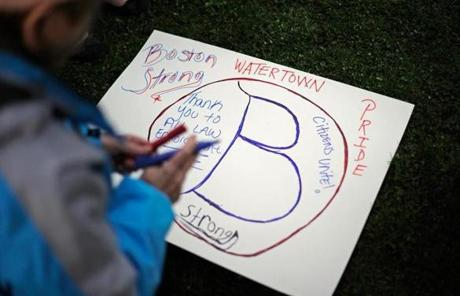 A woman made a sign during a candlelight vigil for victims of the Boston Marathon bombing at Watertown's Victory Park.