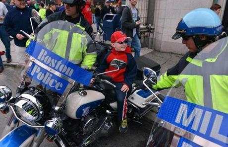 Boston police officer Tim Hicks gave 6-year-old Shane Evans a turn on the seat of his motorcycle outside Fenway Park.