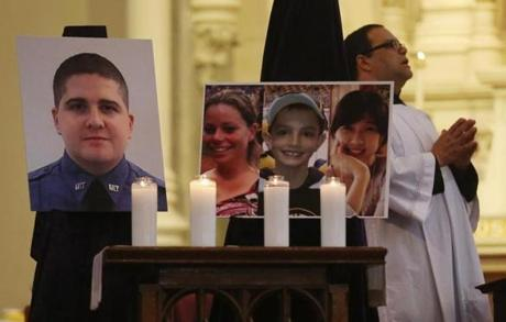Photos of the deceased were displayed today during Mass at the Cathedral of the Holy Cross in Boston.