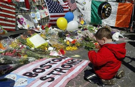 Two-year-old Wesley Brillant of Natick knelt in front of a memorial near the scene of the blasts on Boylston Street.