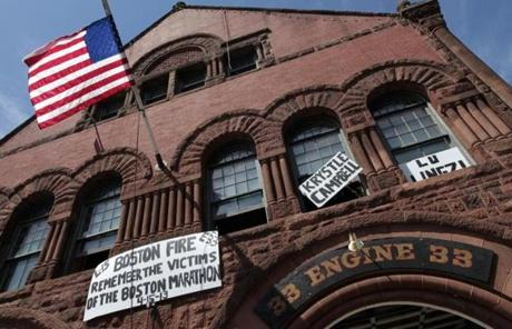 Firefighters from the Boylston Street Firehouse hung signs honoring the victims.