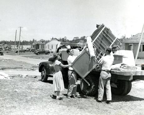 June 9, 1953:  Lenore Bernard of Holden assists the salvage crew with loading a few of her remaining possessions. Her home in the Brentwood Estate section of Holden was badly damaged in the the Great Worcester Tornado. Mrs. Bernard and her daughter Nancy, 16 months old, escaped injury by huddling in the fireplace.