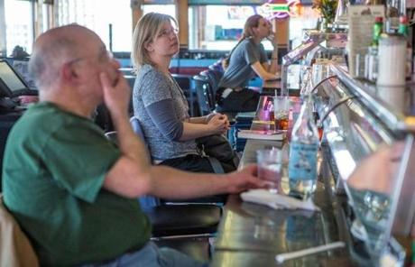 Kerry Milaszewski (center) of Brighton, and other patrons watched TV coverage of Monday's moment of silence at the Deluxe Town Diner in Watertown.