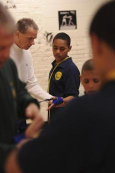 Volunteer coach Arthur Ciriello wraps 13-year-old Dotaderito Rosa's hands before he boxes at St. Peter's Teen Center.
