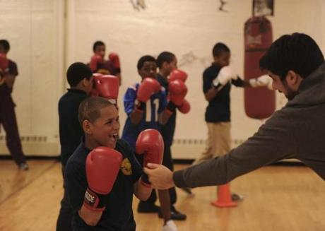 Fabio Rosa, 12, works with volunteer coach Johnathan LoPorto in a boxing class at the Teen Center.