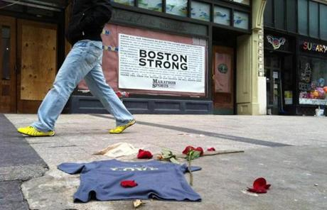 A T-shirt and roses were left near the site of the first bomb on Boylston Street on Wednesday.