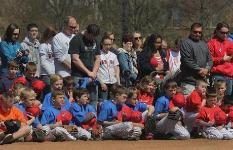 Parents and children held a moment of silence before the start of Little League play.