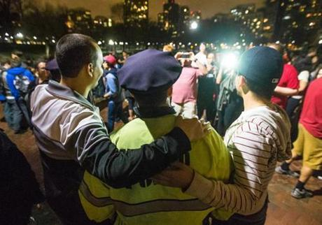 After the arrest, police officers were cheered as heroes. One of them posed with admirers on Boston Common.