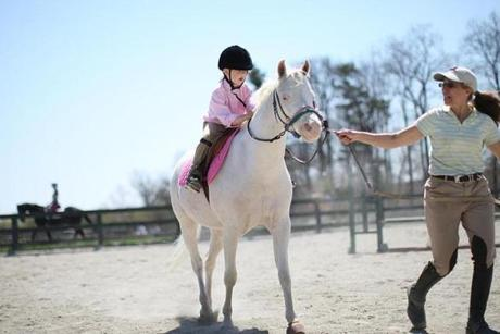 Calle gets riding lessons in Georgetown from Anita Coons, who donates her time and use of her albino pony, Sinatra.