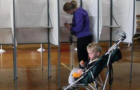 At the Bridgewater Middle School,  Rebecca Johnson voted as her son, Kyle, ate a snack.