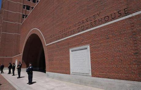 Officers stood outside the Moakley courthouse before the suspects were brought to court.