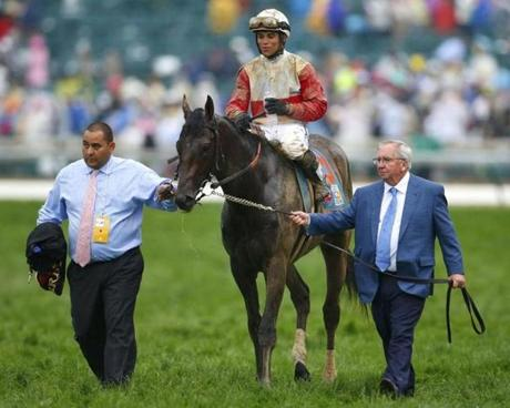 Trainer Claude McGaughey (right) walked his horse with Rosario riding to the winner's circle.