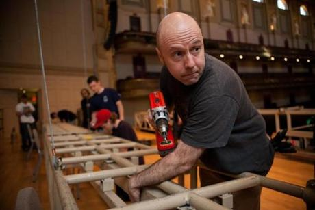 John Moorin (right) works on the lighting assembly as part of the conversion of the Symphony Hall to the Pops cafe table style setup in Boston, Massachusetts on May 5, 2013.