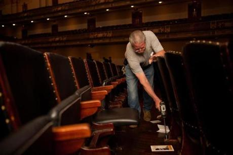 Tom Davenport removes bolts from the base of the seats during the conversion of the Symphony Hall to the Pops cafe table style setup in Boston, Massachusetts on May 5, 2013.