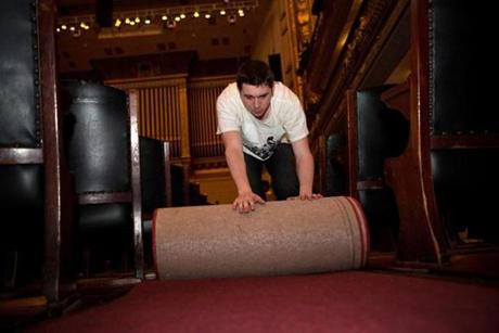 Dillon Doherty rolls up a aisle carpet during the conversion of the Symphony Hall to the Pops cafe table style setup in Boston, Massachusetts on May 5, 2013.
