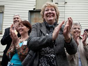 Volunteer Donna Kendall (right) leads the applause at the opening of a Beverly day center for the homeless (left).