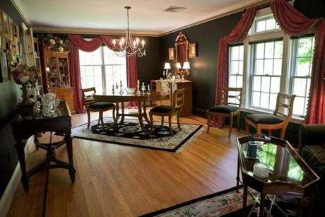 The formal living room and dining area, off the entrance, has oak floors with brown inlaid trim and three banks of large windows.
