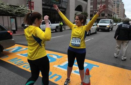 Dana Farber charity runners Sharon Novick (left) and Jessica Cohen celebrated after crossing the finish line a month after the Boston Marathon. They were stopped at the 25.5 mile mark due to the bombing and unable to finish on Marathon Day.