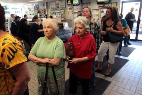 The jackpot for Powerball set a record on Friday as it exceeded $600 million, bringing buyers out for Saturday night's drawing. Sisters Connie Cataldo (left) and Susan Fox, of Derry, N.H., were part of a long line of players in Methuen.
