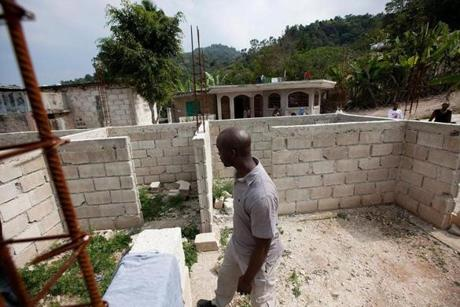 Harold Roy walked through his family's compound, where his grandfather's home is being rebuilt.
