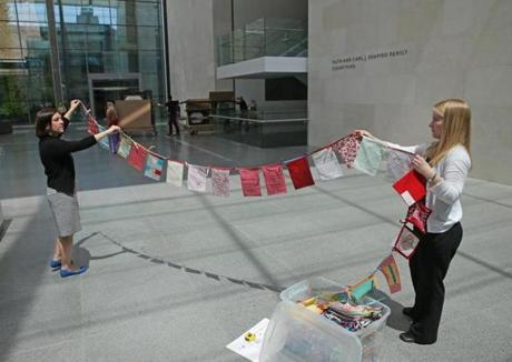 Amy Friend (right) and MFA designer Kyla Hygysician held a number of the small flags that will make up the exhibit.