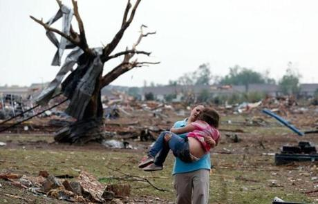 A woman carried her child through a field near the collapsed Plaza Towers Elementary School.