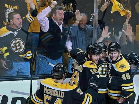 Adam McQuaid, Nathan Horton, and David Krejci (46) mob Torey Krug after his first-period goal; the fans are happy, too.