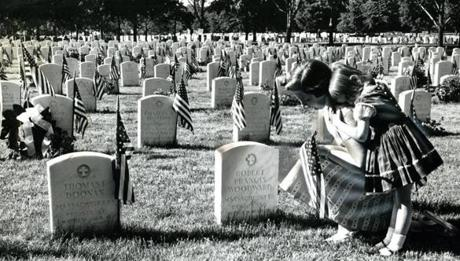 May 30, 1962:  A kneeling woman and her child remembered the war dead at Mt. Hope Cemetery in Mattapan. Notice the woman's hairline was altered with an airbrush, something that was often done at that time for better photo reproduction in the paper.