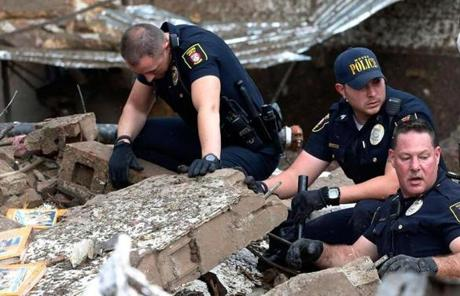 Police officers in Moore, Okla., dug through the rubble of Plaza Towers Elementary School after a massive tornado struck.