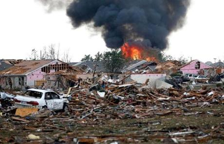 A fire burned amid devastation in Moore, Okla., after an EF-4 tornado with winds up to 200 mph struck there.