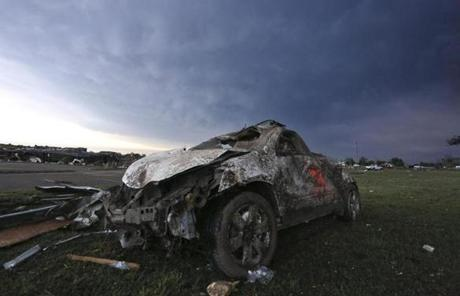 A mangled in the parking lot of Warren Theatre as a storm cloud passed over  early Tuesday in Moore, Okla.