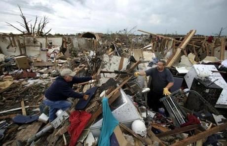 Dalton Sprading (right) salvaged items from his tornado-ravaged home Tuesday in Moore, Okla.