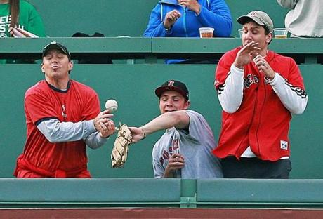 5/28/13: Boston, MA: Niether the fan with the glove in the middle, nor the two around him could make the play on a top of the first inning solo home run into the first row of the Monster Seats by the Phillies Michael Young (not pictured). The ball fell back onto the field as Young rounded the bases to give Philadelphia a 1-0 lead. The Philadelphia Phillies visited the Boston Red Sox in a regular season MLB baseball game at Fenway Park. (Jim Davis/Globe Staff) section: sports topic: Sox-Phillies (1)