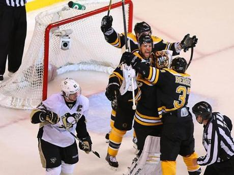 Boston Bruins goalie Tuukka Rask celebrated with Dennis Seidenberg, Brad Marchand, and Patrice Bergeron after winning game 4 of the Eastern Conference Finals while the Penguins'  Sidney Crosby skated by.