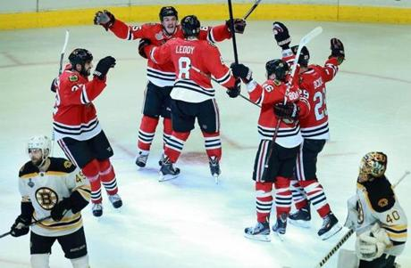 Chicago Blackhawks center Andrew Shaw (second from left) celebrated after he tipped the puck past Bruins goalie Tuukka Rask (40) for the winning goal in the third overtime period of game one of the Stanley Cup Finals.