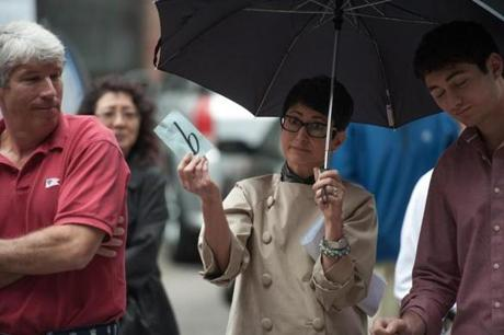 Bidders and spectators stood out in the rain Thursday during the parking-space auction.