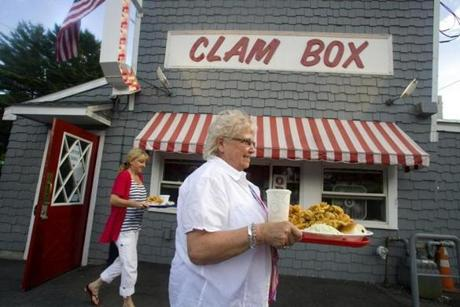 MaryBeth Walters of Cooperburg, Pa., carries a fried clam dinner from the Clam Box in Ipswich.