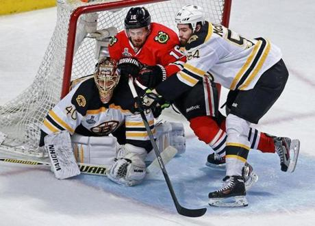 Bruins goalie Tuukka Rask has some unwanted company in the Blackhawks' Marcus Kruger, but Adam McQuaid does his best to clear the crease.