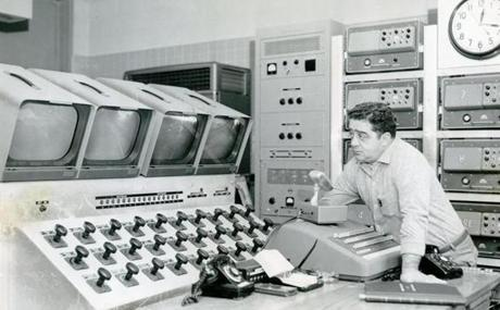 November 4, 1959: A complete closed circuit television and paging system was installed in the tunnel which linked the Central Artery and the Southeast Expressway. The TV system consisted of eight television pick-up cameras in each tube of the tunnel which were then connected to the television monitors in the control building. Charles Sperrazza monitored the system here for any motorist needing aid or other type of mechanical trouble. He could also call out instructions to motorists by means of a public address system. This was of special value in case of a bad accident or fire in which which panic and confusion could be a factor.