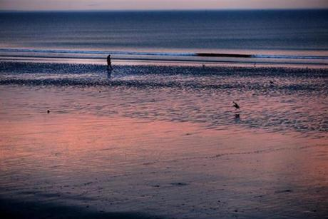 Sunlight was reflected through hazy morning clouds at sunrise at Nantasket Beach.
