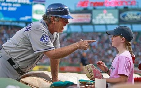 Colorado Rockies first-base coach Rene Lachemann gave a young fan a souvenir baseball between innings of a game hosted by the Red Sox at Fenway Park.
