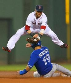 Dustin Pedroia leaped over Blue Jays runner Jose Bautista at second base as he fired to first base to complete a double play in the fourth inning against Toronto at Fenway Park.
