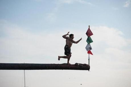 Nicolas Alves won the greasy pole contest during the St. Peter's Fiesta in Gloucester.