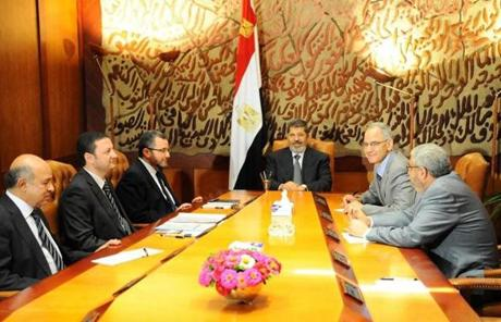 This image released by the office of the Egyptian Morsi (center) met with members of his government in Cairo on Monday.