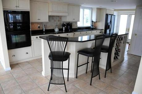 The kitchen has black granite counters and a breakfast island, and flows into the living room.