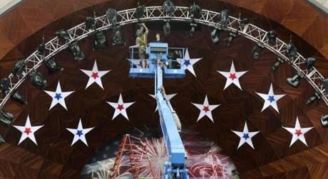 Workers set the lighting on the facade of the Hatch  Shell on Tuesday.