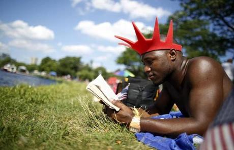 Matt Kimm, 21, of Boston read a book along the Esplanade as he waited for the fireworks.
